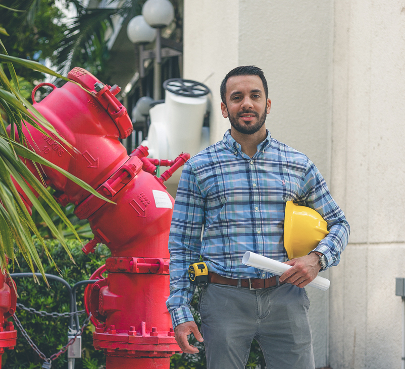 Alejandro is standing next to a big red pipe.
