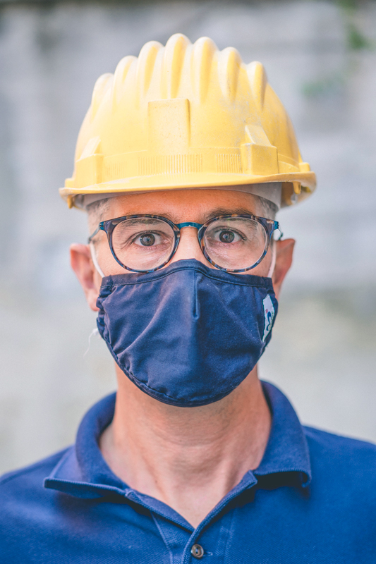 Alessandro is looking into the camera wearing a security helmet. He also wears a mask for covid protection.