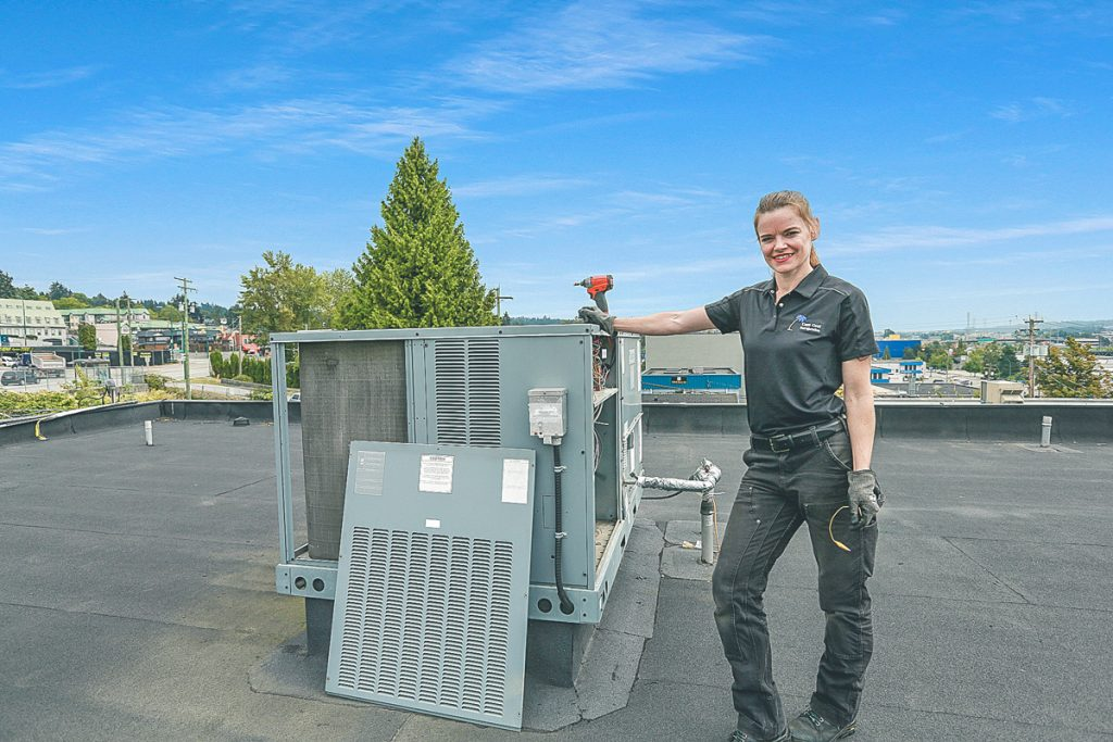 Jessica standing next to an HVAC roof unit.