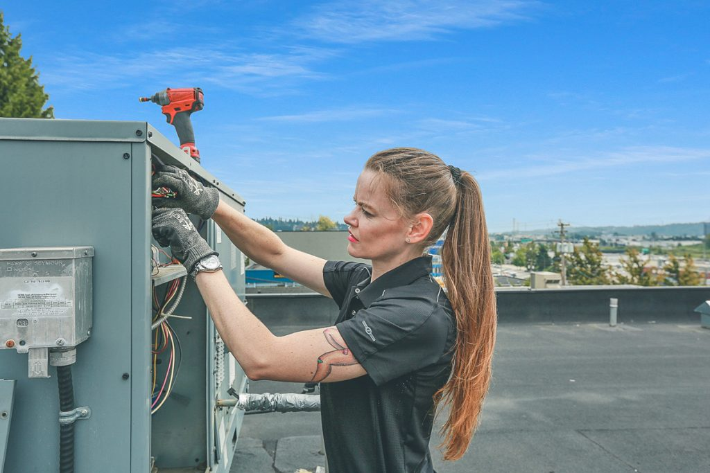 Jessica is hand-on on the HVAC roof unit.