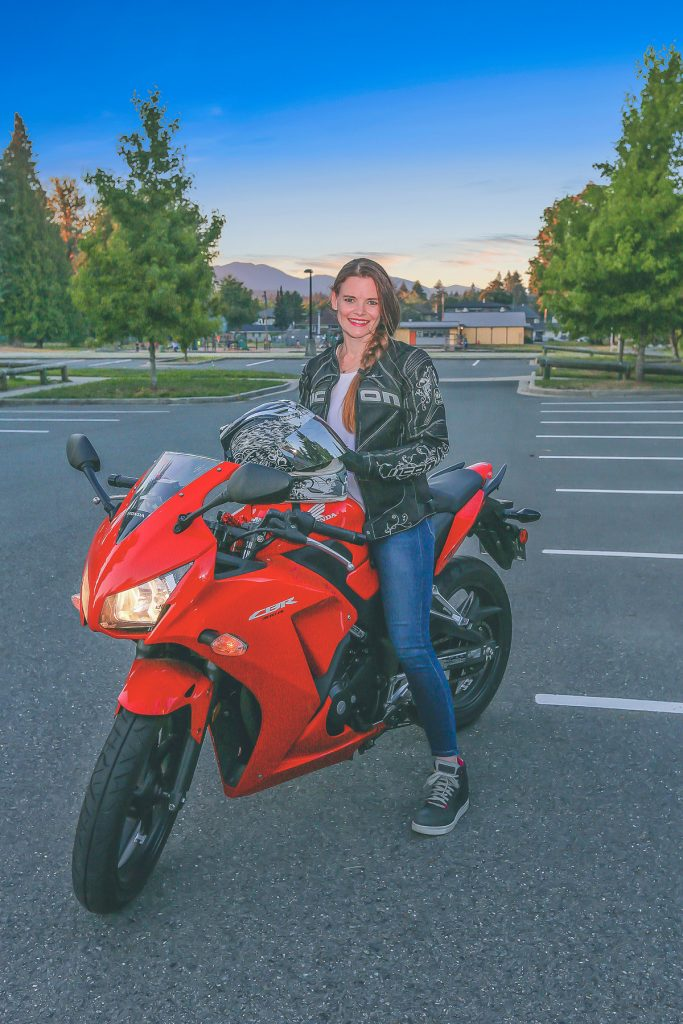 Jess is smiling at the camera while on top of her red motorbike.