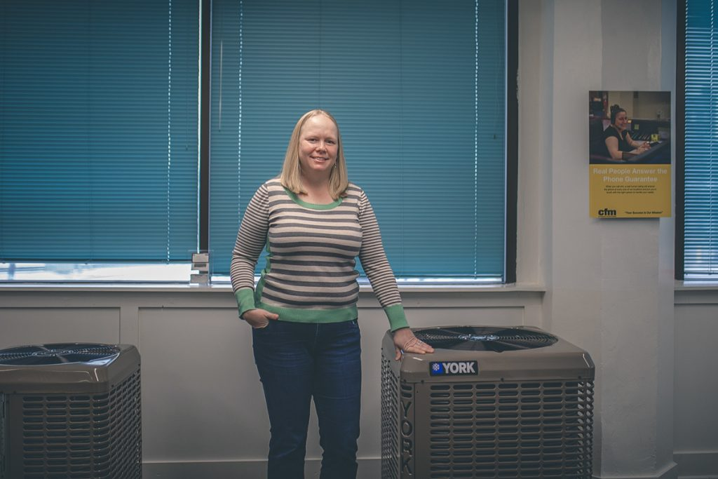 Picture of Lauren, she is standing between two York HVAC units.