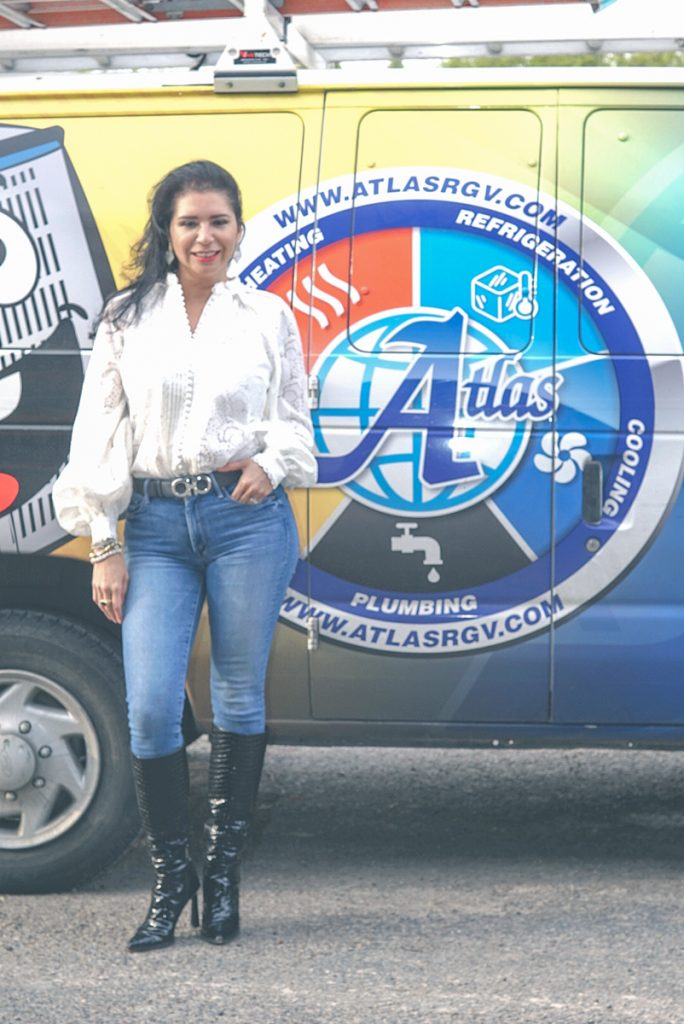 Sarah is in front of one of the work vans from Atlasrgv.