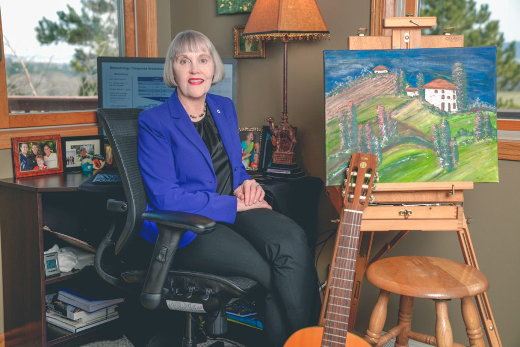 Renee is sitting next to a beautiful painting. Below the painting is a musical instrument. It looks like a classical guitar.